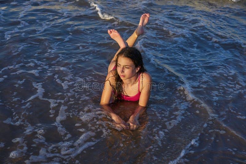 Mentira relajada de la muchacha del bikini en la arena de la playa imágenes de archivo libres de regalías