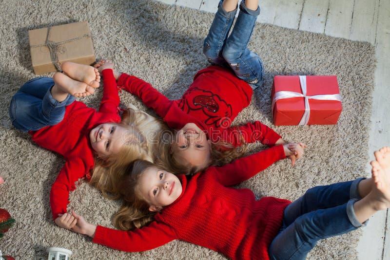 Mentira rubia de tres niñas en los regalos del árbol de navidad del Año Nuevo del piso foto de archivo