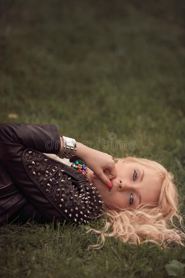 Mentira rubia en la hierba retrato de la mujer en chaqueta de cuero y reloj negros de moda fotografía de archivo libre de regalías
