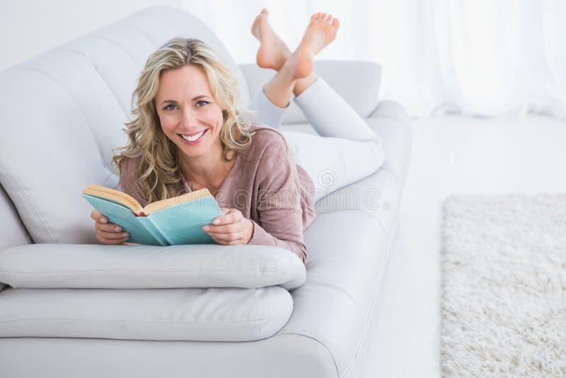 Mentira rubia sonriente en el libro de lectura del sofá imagen de archivo