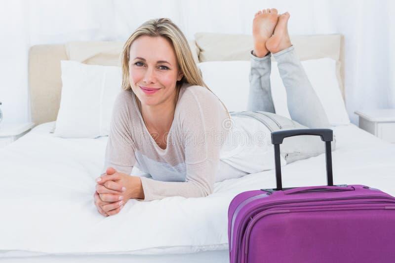 Mentira rubia sonriente en la cama cerca de su equipaje imagen de archivo libre de regalías