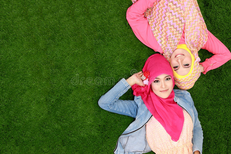 Mentira sonriente de la mujer musulmán feliz hermosa dos en hierba con el poli fotos de archivo