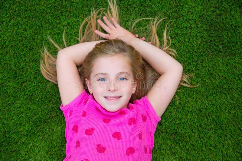 Mentira sonriente del niño de la muchacha rubia hermosa de los niños en hierba imagenes de archivo