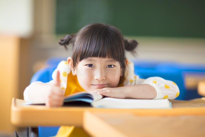 Mentira sonriente del niño propensa en un escritorio y un pulgar para arriba imágenes de archivo libres de regalías
