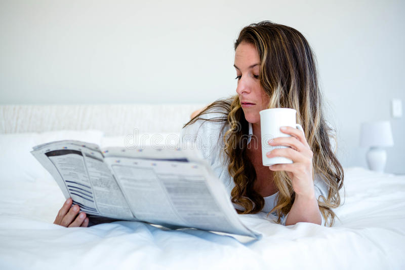 mentira womaan en la cama que lee el newspaaper imagenes de archivo