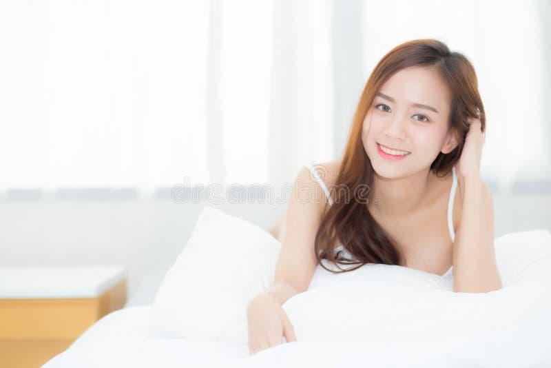 Mentira y sonrisa asiáticas jovenes de la mujer del retrato hermoso mientras que despierte con salida del sol en la mañana imagen de archivo libre de regalías