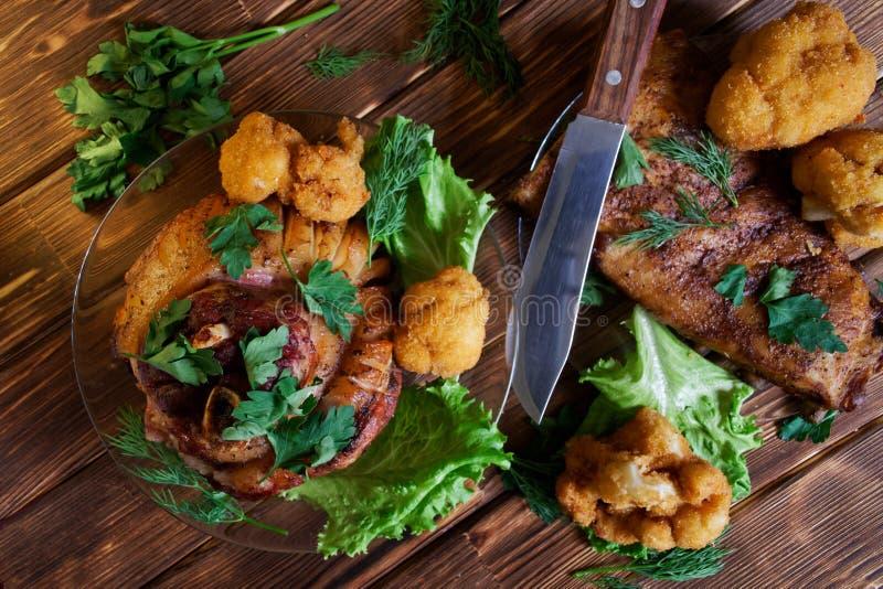 Mentiras cozidas deliciosas da carne em uma tabela rústica feita de placas naturais do pinho Junta, alface, salsa, couve-flor e a fotografia de stock royalty free