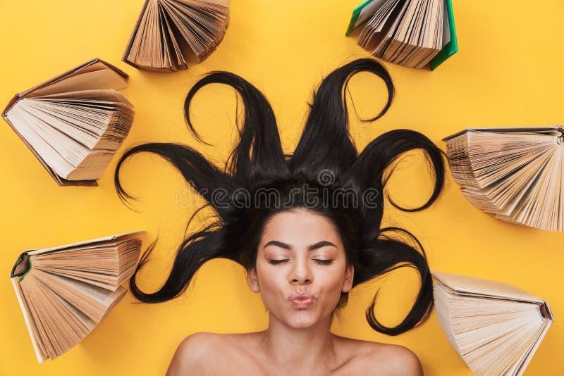 Mentiras da jovem mulher isoladas no fundo amarelo sobre os livros que fundem beijos foto de stock royalty free