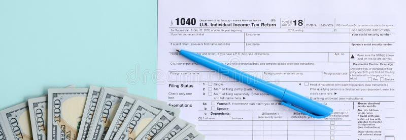 1040 mentiras de la forma de impuesto cerca de cientos billetes de dólar y de la pluma azul en un fondo azul claro Declaración so imagen de archivo