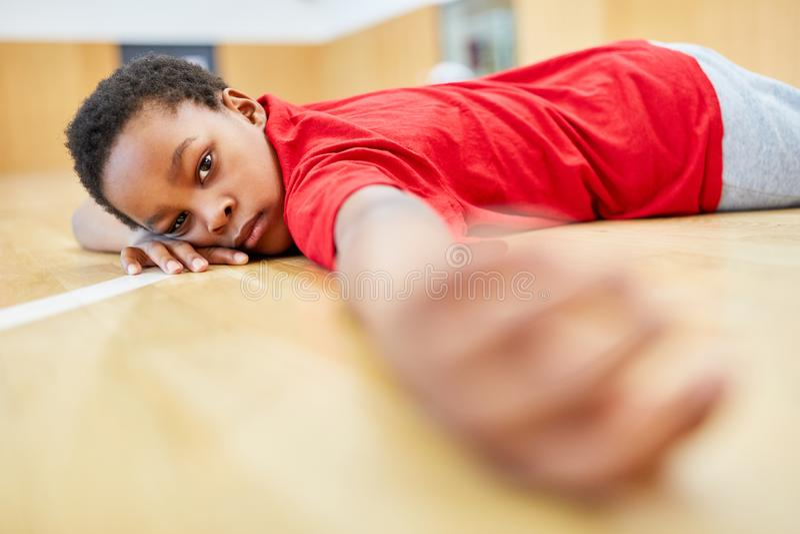Mentiras del muchacho agotadas en el gimnasio fotografía de archivo
