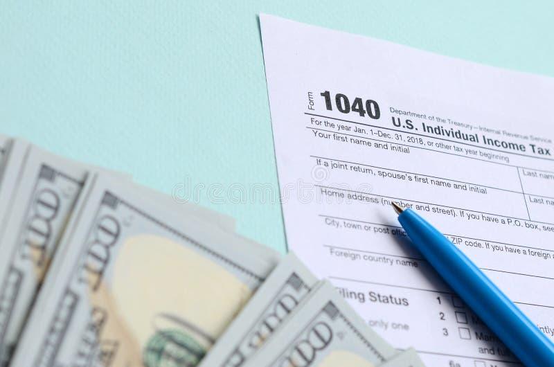 1040 mentiras do formulário de imposto perto de cem notas de dólar e da pena azul em um claro - fundo azul Declaração de rendimen imagens de stock royalty free