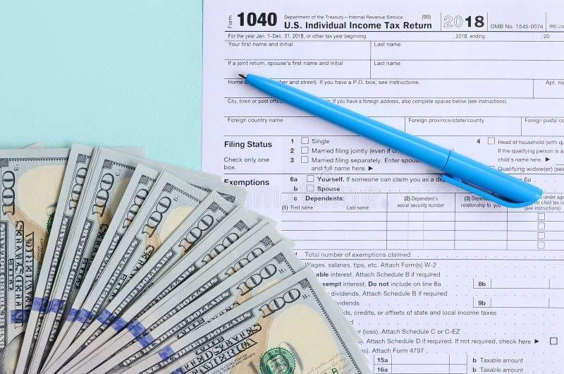 1040 mentiras do formulário de imposto perto de cem notas de dólar e da pena azul em um claro - fundo azul Declaração de rendimen fotografia de stock royalty free