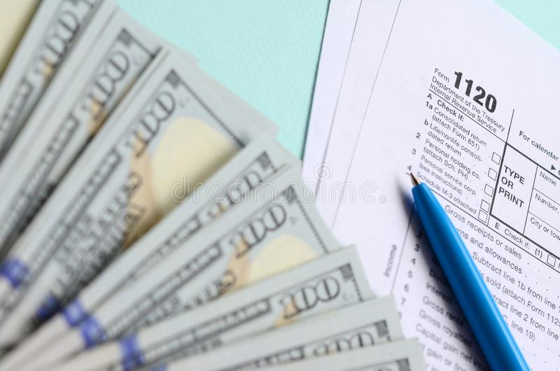1120 mentiras do formulário de imposto perto de cem notas de dólar e da pena azul em um claro - fundo azul Declaração de rendimen fotos de stock royalty free