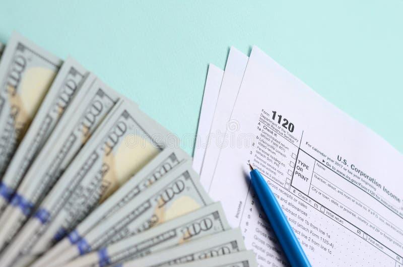 1120 mentiras do formulário de imposto perto de cem notas de dólar e da pena azul em um claro - fundo azul Declaração de rendimen fotografia de stock