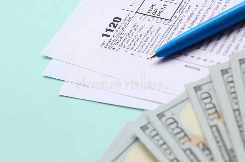 1120 mentiras do formulário de imposto perto de cem notas de dólar e da pena azul em um claro - fundo azul Declaração de rendimen imagem de stock royalty free