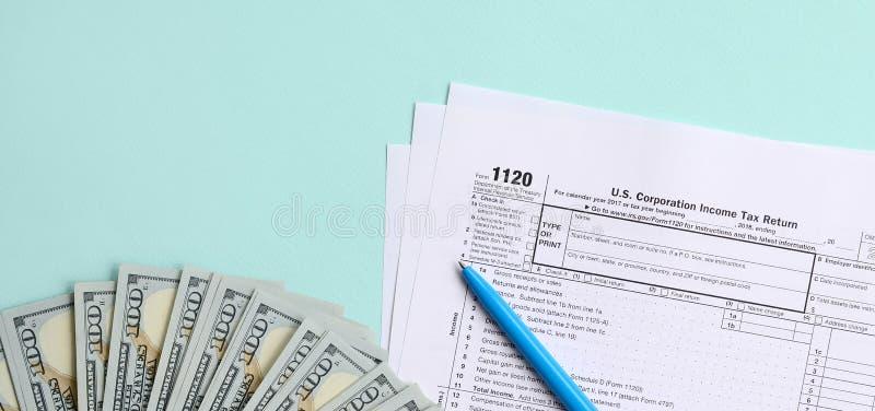 1120 mentiras do formulário de imposto perto de cem notas de dólar e da pena azul em um claro - fundo azul Declaração de rendimen imagens de stock