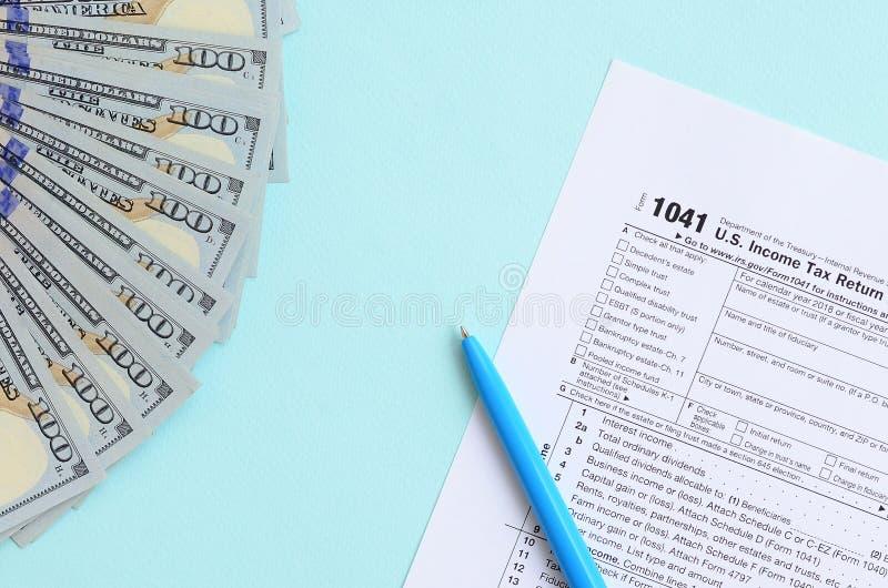 1041 mentiras do formulário de imposto perto de cem notas de dólar e da pena azul em um claro - fundo azul Declaração de rendimen imagem de stock