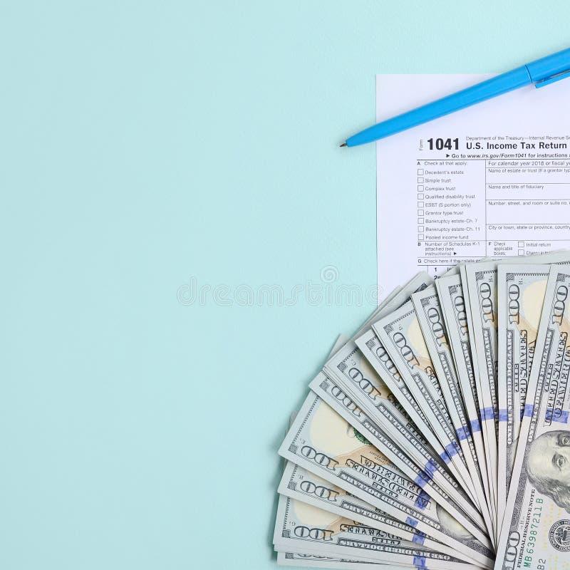 1041 mentiras do formulário de imposto perto de cem notas de dólar e da pena azul em um claro - fundo azul Declaração de rendimen fotos de stock