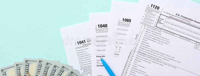 Mentiras dos formulários de imposto perto de cem notas de dólar e da pena azul em um claro - fundo azul Declaração de rendimentos fotos de stock