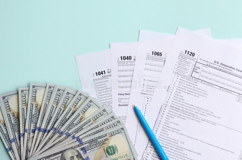 Mentiras dos formulários de imposto perto de cem notas de dólar e da pena azul em um claro - fundo azul Declaração de rendimentos fotos de stock royalty free
