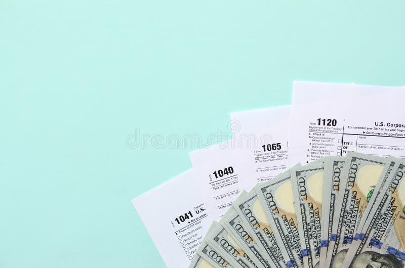 Mentiras dos formulários de imposto perto de cem notas de dólar e da pena azul em um claro - fundo azul Declaração de rendimentos imagem de stock royalty free