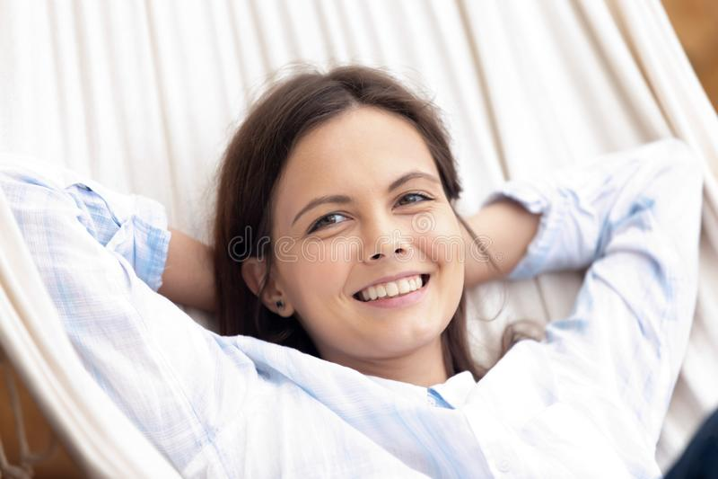 Mentiras femeninas serenas felices en la hamaca que descansa al aire libre foto de archivo