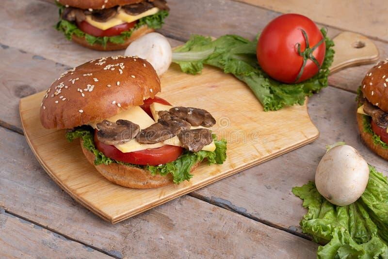 Mentiras fritadas suculentas dos cogumelos no queijo e no tomate fotografia de stock