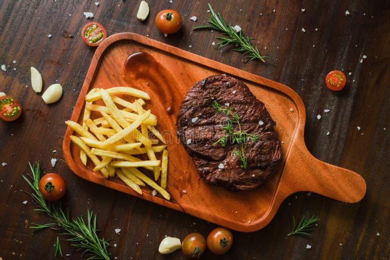 Mentiras grelhadas no espeto grelhadas do bife da carne com frieson francês uma cutelaria de madeira elegante velha rústica que c fotos de stock royalty free