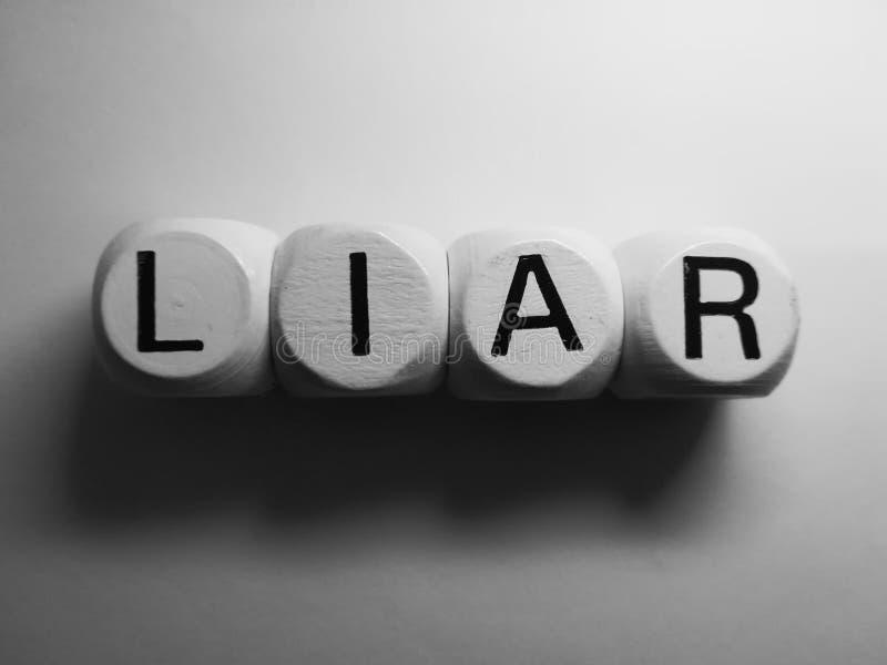 Mentiroso de la palabra deletreado en dados fotos de archivo libres de regalías