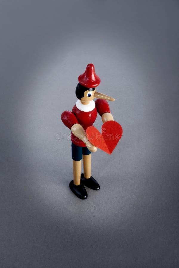 Mentiroso de Pinocchio que guarda o coração fotos de stock