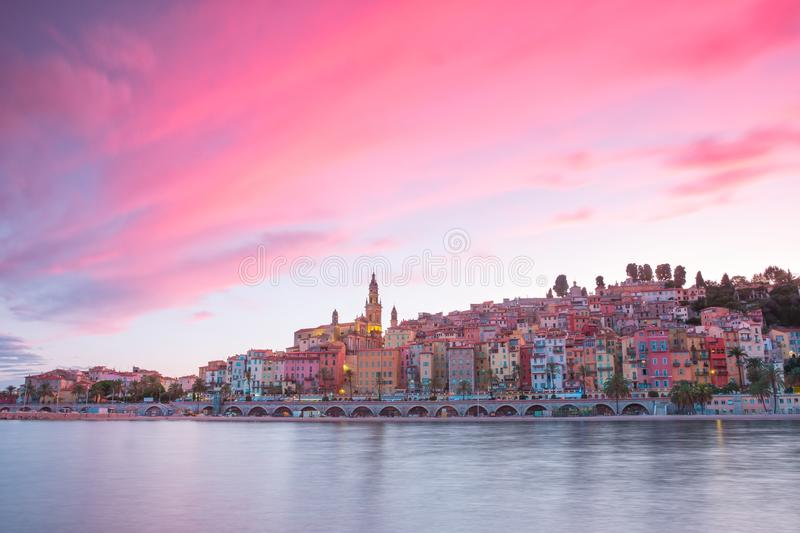 Menton City at night, French Riviera, golden hour before sunset. Mood, lights reflecting on sea water surface, pink sky royalty free stock photo