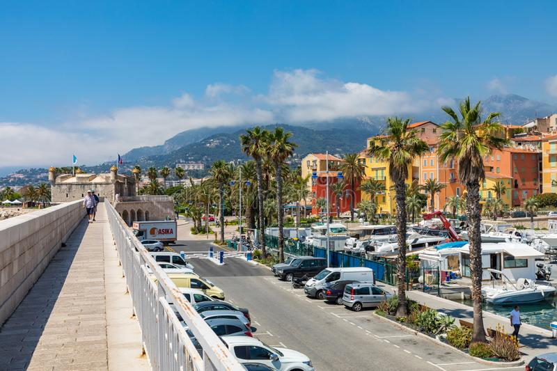 MENTON, FRANCE - JUNE 05, 2019: View of palm tree and harbor with boats in Menton on French Riviera. Provence-Alpes-Cote d`Azur,. France royalty free stock photography