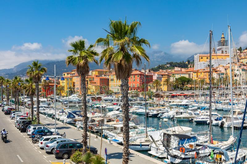 MENTON, FRANCE - JUNE 05, 2019: View of palm tree and harbor with boats in Menton on French Riviera. Provence-Alpes-Cote d`Azur,. France stock photography