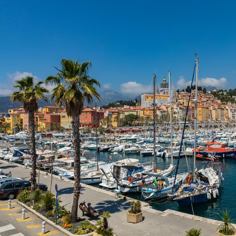 MENTON, FRANCE - JUNE 05, 2019: View of palm tree and harbor with boats in Menton on French Riviera. Provence-Alpes-Cote d`Azur,. France royalty free stock image