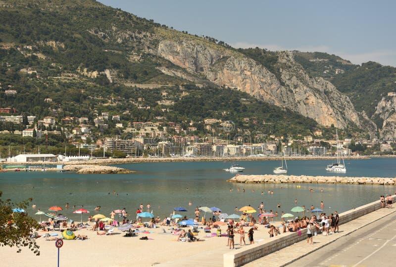 Menton Frankrike - Juni 18, 2019: Folket vilar på stranden av Menton på Cote d'Azur av franska Riviera royaltyfri foto