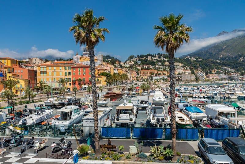 MENTON FRANKRIKE - JUNI 05, 2019: Sikt av palmträdet och hamnen med fartyg i Menton på franska Riviera Provence-Alpes-skjul D 'Az arkivfoto