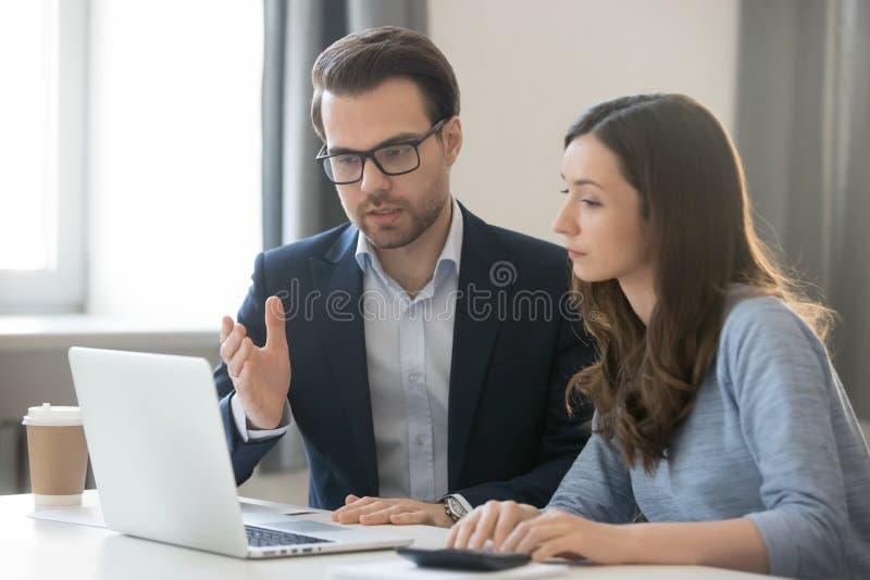 Mentor útil do chefe que explica o projeto em linha novo ao interno do trabalhador imagens de stock royalty free