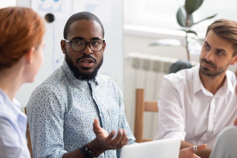 Mentor africano serio que explica nueva estrategia de los internos caucásicos en el encuentro fotografía de archivo libre de regalías