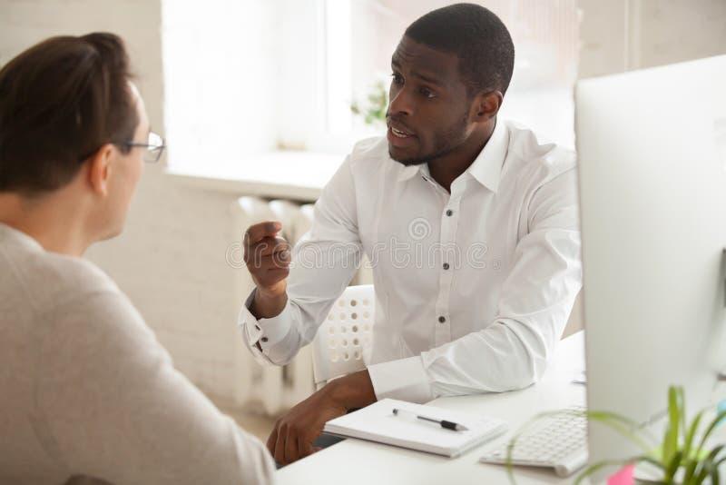 Mentor afro-americano que explica a ideia nova ao employe caucasiano imagens de stock