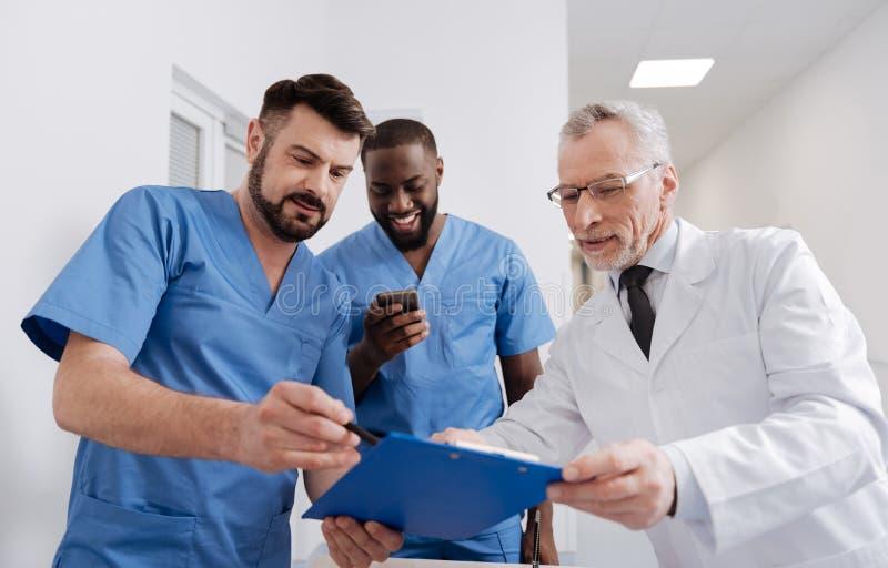 Mentor amigável de envelhecimento que verifica o relatório dos internos no hospital imagem de stock