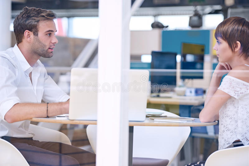 Mentor busy tutoring his female student in co-work space. Male tutor busy mentoring his bright female student in colourful co-work space busy using his notebook stock photo