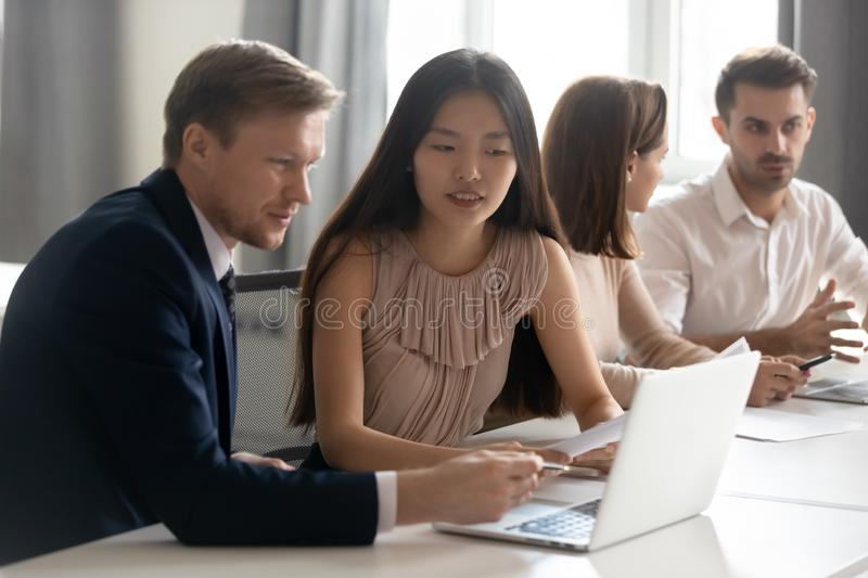 Mentor coach helping Asian female employee with corporate software stock images
