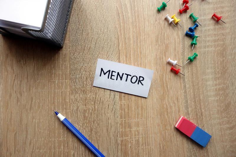 Mentor concept. With message on wooden table royalty free stock photos