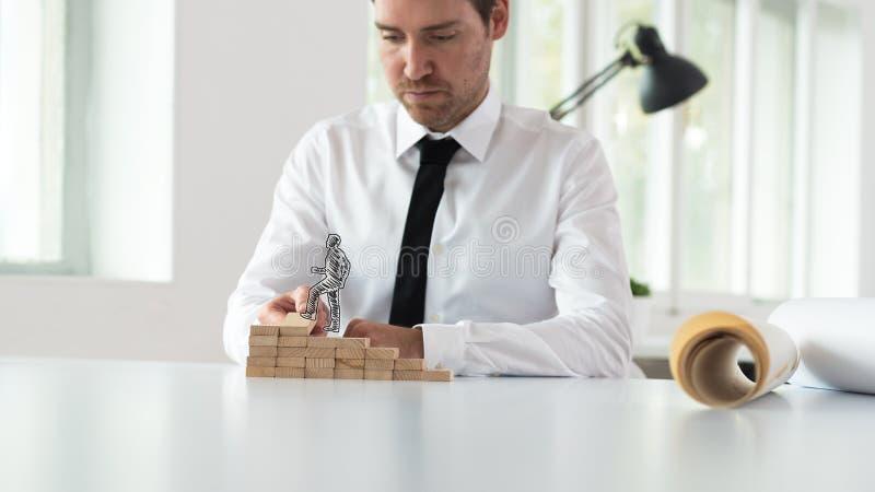 Mentor de negócio que monta etapas de madeira para um homem de negócios mostrado em silhueta foto de stock royalty free