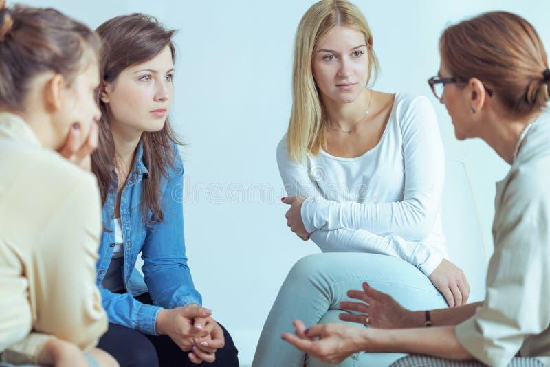 Mentor, der mit Geschäftsfrauen über Karriere während des Seminars mit Training spricht stockbilder
