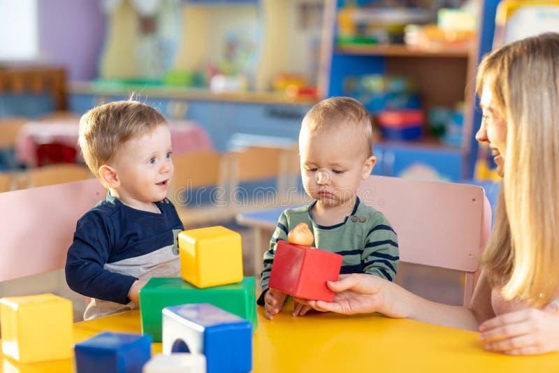 Mentor e bebês que têm o divertimento no jardim de infância Professor, educação, crianças e conceito da escola primária foto de stock