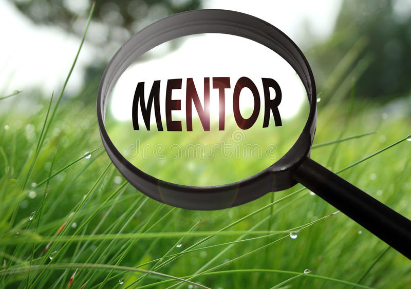 Mentor. Magnifying glass with the word mentor on grass background. Selective focus royalty free stock photography