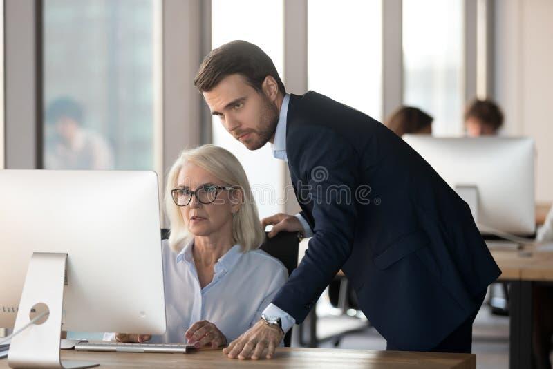 Mentor masculin sérieux dirigeant l'employé féminin aider avec le problème d'ordinateur photo libre de droits