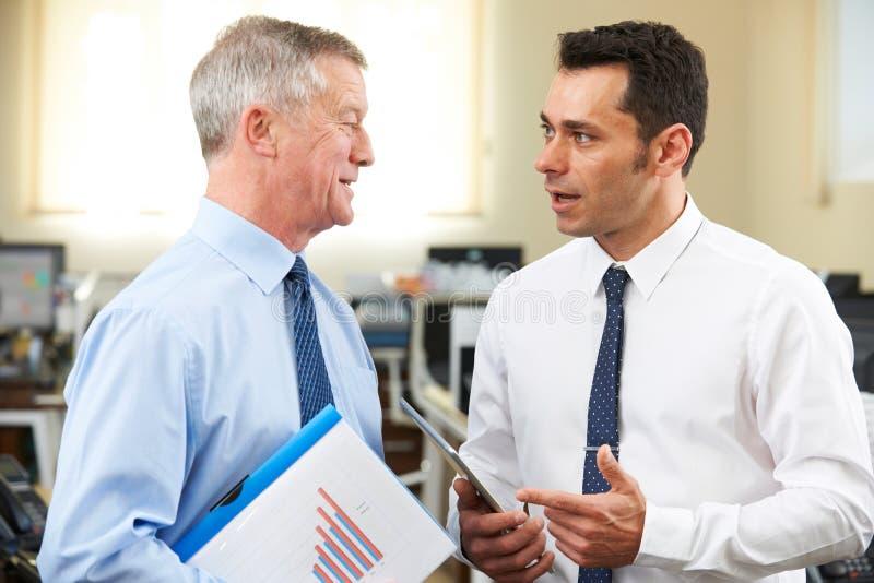 Mentor mayor de Having Discussion With del hombre de negocios en oficina imagenes de archivo