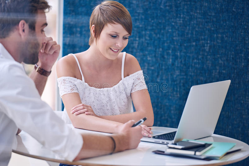 Mentorship between male tutor and female student using modern laptop royalty free stock photo
